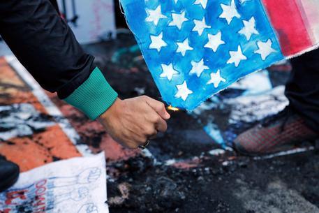 Iran, migliaia di persone in piazza bruciano una bandiera Usa